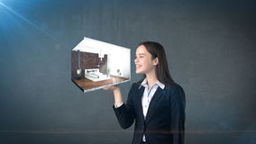 Portrait of young woman holding 3d interior on the open hand palm, over isolated studio background. Business concept. Royalty Free Stock Images