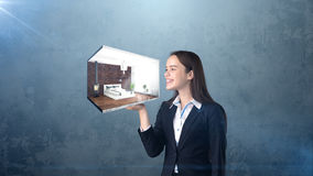 Portrait of young woman holding 3d interior on the open hand palm, over isolated studio background. Business concept. Royalty Free Stock Photography
