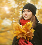 Portrait of a young woman holding fallen leaves Stock Photo
