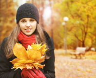 Portrait of a young woman holding fallen leaves Royalty Free Stock Images