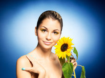 Portrait of a young woman holding a flower on blue Stock Image