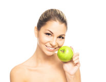 Portrait of a young woman holding a fresh green apple. Portrait of a young and attractive Caucasian woman holding a fresh green apple. The image is taken in a Royalty Free Stock Image