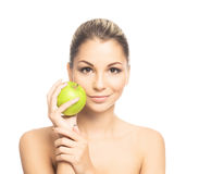 Portrait of a young woman holding a fresh green apple. Portrait of a young and attractive Caucasian woman holding a fresh green apple. The image is taken in a Royalty Free Stock Photography