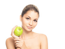 Portrait of a young woman holding a fresh green apple. Portrait of a young and attractive Caucasian woman holding a fresh green apple. The image is taken in a Royalty Free Stock Images