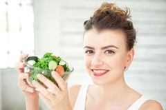 Portrait of a young woman holding a fresh salad bowl in white room. Royalty Free Stock Photo