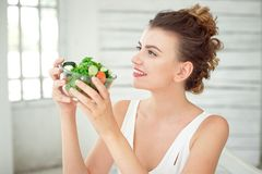 Portrait of a young woman holding a fresh salad bowl in white room. Royalty Free Stock Photography