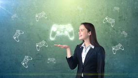 Portrait of young woman holding gamer`s joystick on the open hand palm, over drawn studio background. Business concept. Portrait of young longhair brunette Royalty Free Stock Photography