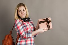 Portrait of a young woman holding a gift. Student in checkered s royalty free stock photos