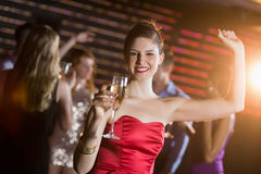 Portrait of young woman holding a glass of champagne while dancing Royalty Free Stock Photo