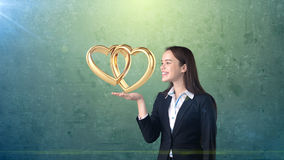 Portrait of young woman holding golden wedding rings on the open hand palm, isolated studio background. Business concept Stock Photography