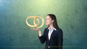 Portrait of young woman holding golden wedding rings on the open hand palm, isolated studio background. Business concept Royalty Free Stock Image