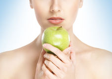 Portrait of a young woman holding a green apple Stock Photography