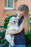 Portrait of Young woman holding on hands puppy Labrador Stock Image