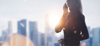 Portrait of young woman holding her smartphone in a hands. Blurred city on the background. Wide Stock Image