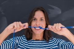 Woman holding a internet cable in front of chalk drawing board Stock Photo