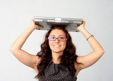 Portrait of young woman holding laptop. Portrait of young woman holding a laptop above her head royalty free stock image