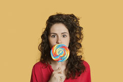Portrait of a young woman holding lollipop in front of face over colored background Royalty Free Stock Photos