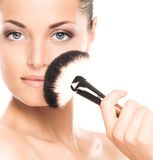 Portrait of a young woman holding a makeup brush Stock Image
