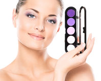 Portrait of a young woman holding a makeup pallette Stock Photos