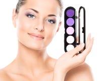 Portrait of a young woman holding a makeup pallette Stock Photos