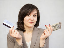 Portrait of a young woman holding money and plastic card Royalty Free Stock Images