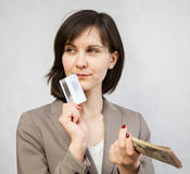 Portrait of a young woman holding money and plastic card. On neutral background Royalty Free Stock Images
