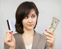 Portrait of a young woman holding money and plastic card Stock Photos