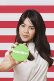 Portrait of young woman holding out volunteer badge against American flag Royalty Free Stock Image