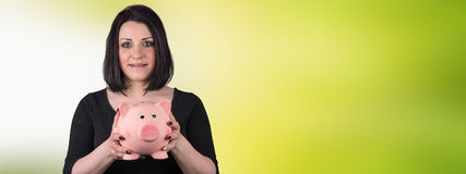 Portrait of young woman holding a piggy bank. On blurred background Royalty Free Stock Photography