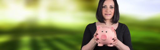 Portrait of young woman holding a piggy bank. On blurred background Stock Photo