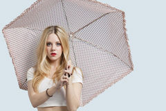 Portrait of young woman holding polka dotted umbrella against light blue background Royalty Free Stock Images