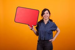 Portrait of young woman holding red thought bubble over yellow background in studio. Cheerful woman with banner in her hand royalty free stock photo