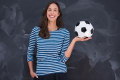 Woman holding a soccer ball in front of chalk drawing board Royalty Free Stock Images