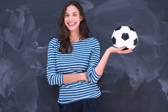Woman holding a soccer ball in front of chalk drawing board Royalty Free Stock Photography