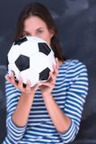 Woman holding a soccer ball in front of chalk drawing board Royalty Free Stock Image