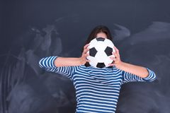 Woman holding a soccer ball in front of chalk drawing board Royalty Free Stock Photo