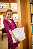 Portrait of young woman holding stack of books in library Royalty Free Stock Photo