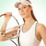Portrait of a young woman holding a tennis raquet. Portrait of a young and sporty Caucasian woman holding a tennis racket. The image is taken on a light blue Stock Images