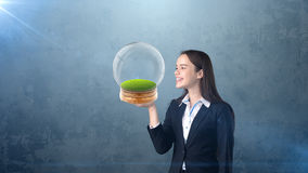 Portrait of young woman holding transparent orb on the open hand palm with empty copyspace. Business concept Stock Image