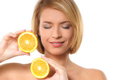 Portrait of a young woman holding two oranges Royalty Free Stock Images