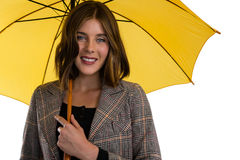 Portrait of young woman holding umbrella. While standing against white background Royalty Free Stock Image
