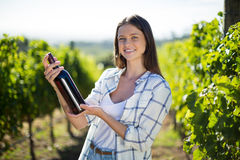 Portrait of young woman holding wine bottle at vineyard Stock Photography