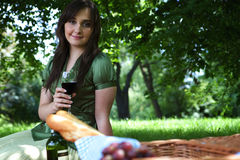 Portrait of young woman holding wineglass, sitting in park Royalty Free Stock Images