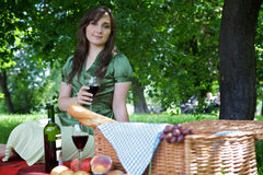 Portrait of young woman holding wineglass, sitting in park Royalty Free Stock Photo