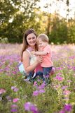 Portrait of young woman hugging her little toddler son on a sunny meadow. Portrait of young women hugging her little toddler son on a sunny meadow. Mum with boy Stock Photography