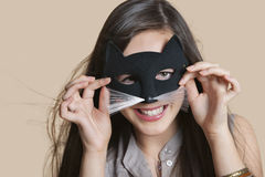 Portrait of a young woman imitating as cat while looking through eye mask over colored background Stock Photos
