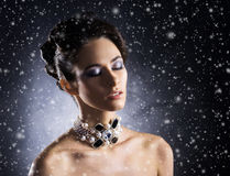 Portrait of a young woman in jewelry on the snow Royalty Free Stock Photos