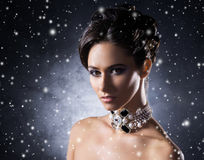 Portrait of a young woman in jewelry on snow Stock Photo