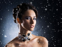 Portrait of a young woman in jewelry on snow Royalty Free Stock Photography