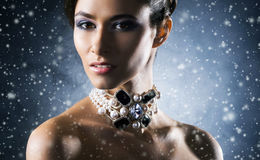 Portrait of a young woman in jewelry on snow Stock Images